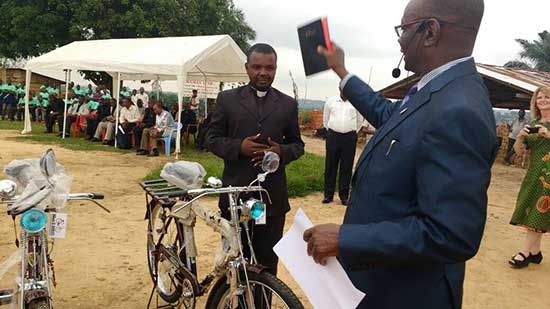 Bishop Unda distributing bicycles and bibles at 2017 East Congo Annual Conference