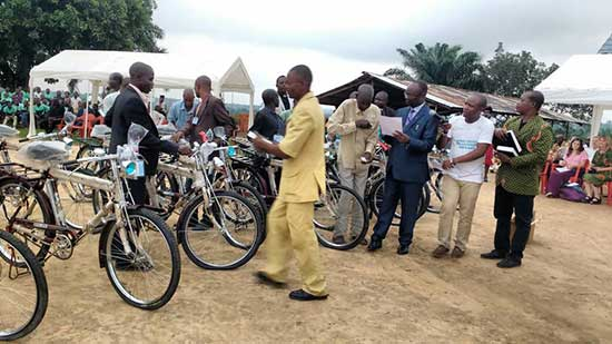 Bishop Unda (blue suite) is awarding bicycles at 2017 East Congo Annual Conference while the Lay Leader, Chief Prosper Tunda (green Jacket) awards the bibles.